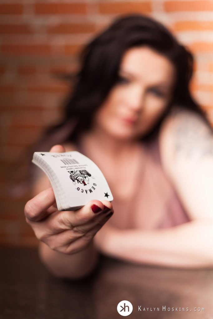 woman in lingerie out of focus while the deck of cards she is holding is closer to camera and in focus
