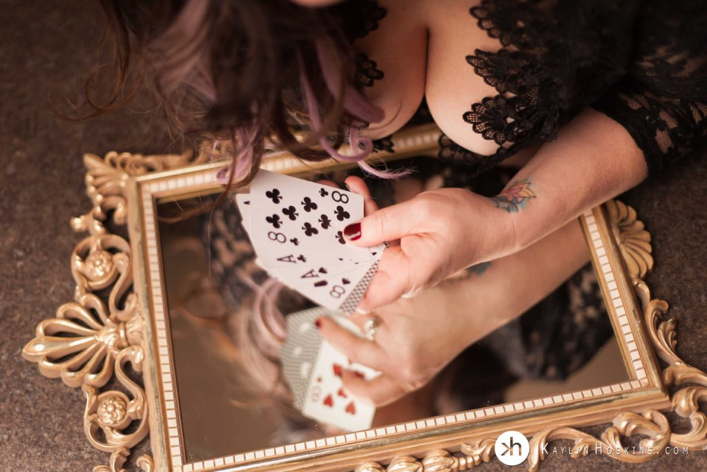 Woman holds playing cards while she leans over old vintage mirror with cleavage and black lingerie during boudoir shoot