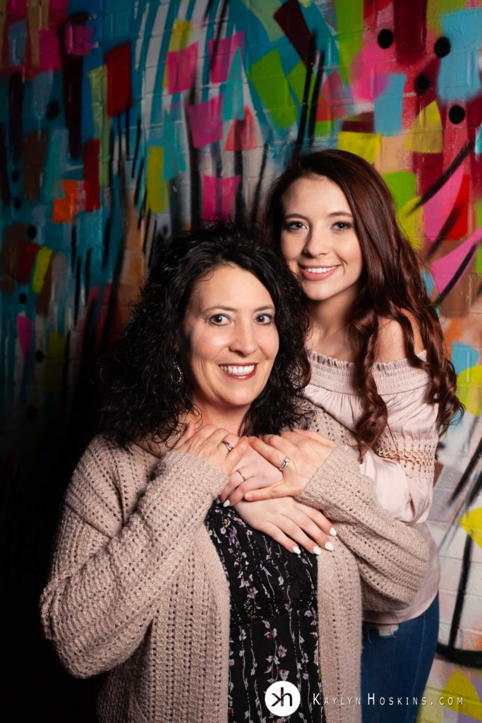 Senior wraps arms around her Mom standing in front of artwork graffiti downtown Iowa City Iowa