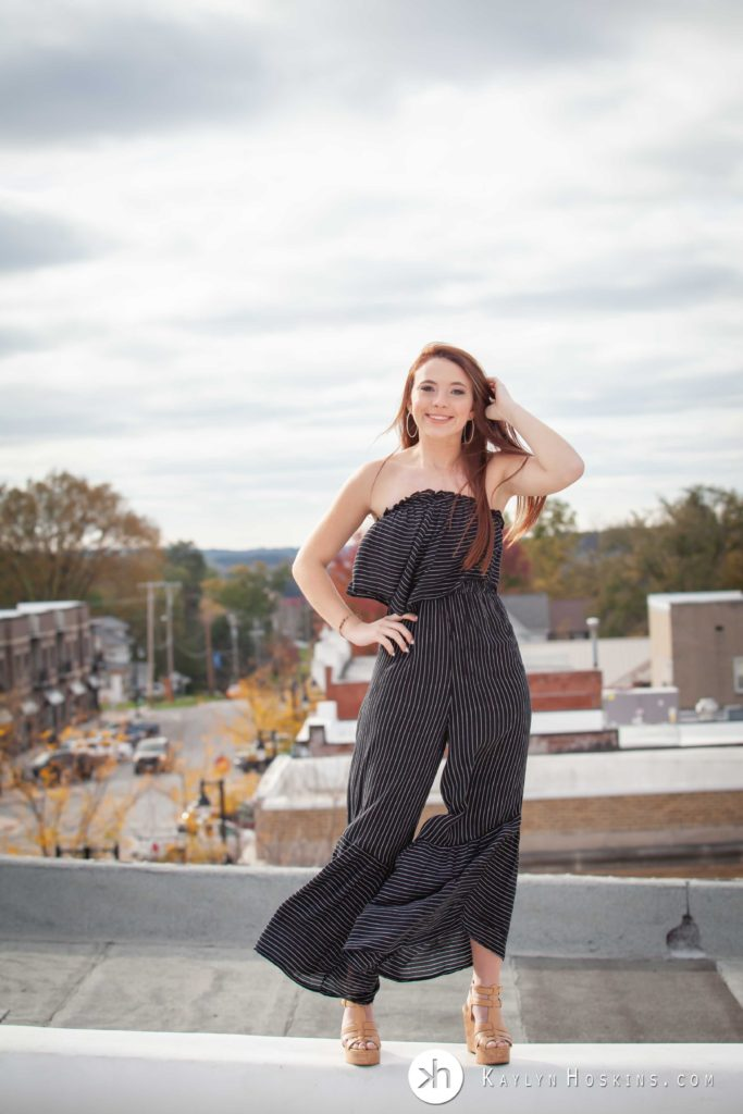 Senior wearing black striped outfit blows in wind with downtown Solon, Iowa in the background