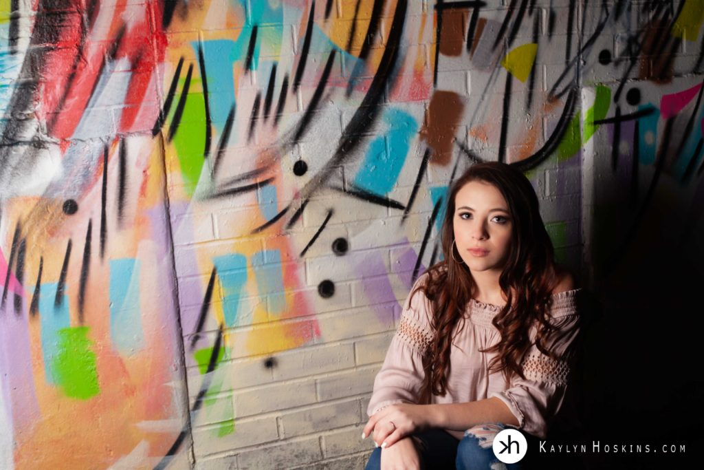 Senior sitting up against art graffiti wall downtown Iowa City photo by Kaylyn Hoskins