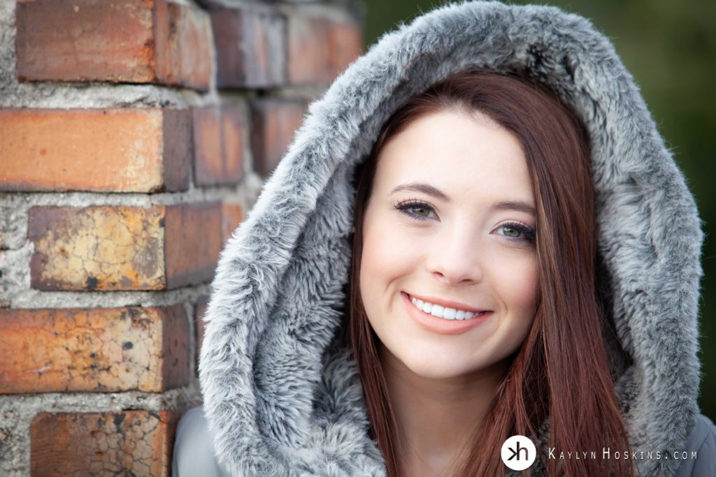 Senior girl wearing grey fur coat with hood up leans up against old chimney on rooftop of Kaylyn Hoskins Photography downtown Solon, Iowa