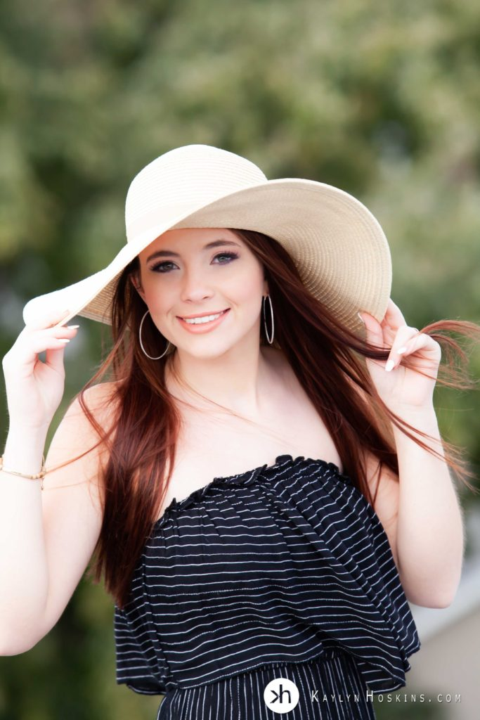 Senior girl playfully holds onto her sun hat on rooftop of Kaylyn Hoskins Photography studio downtown Solon, Iowa