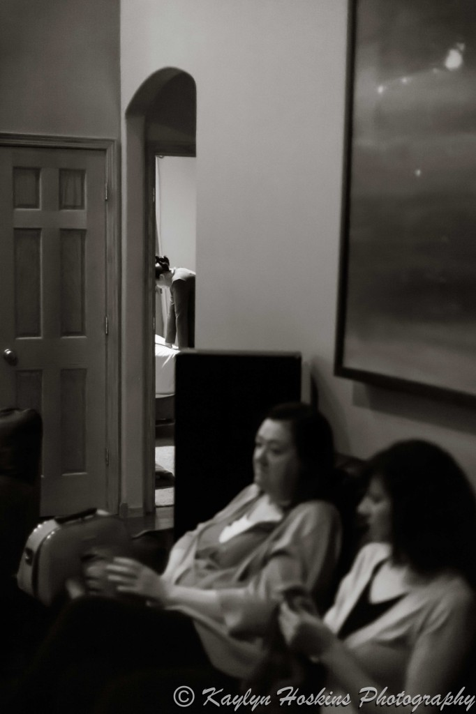 Midwives sit calmly as home birth Mother has contractions in other room