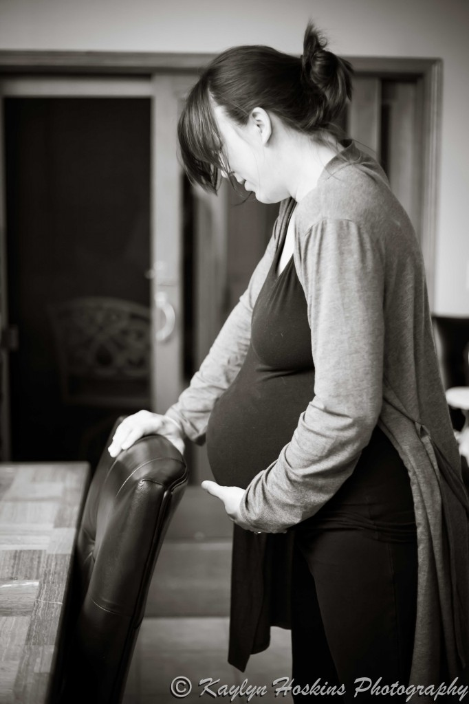 Home birthing Mother holds onto chair during strong contraction