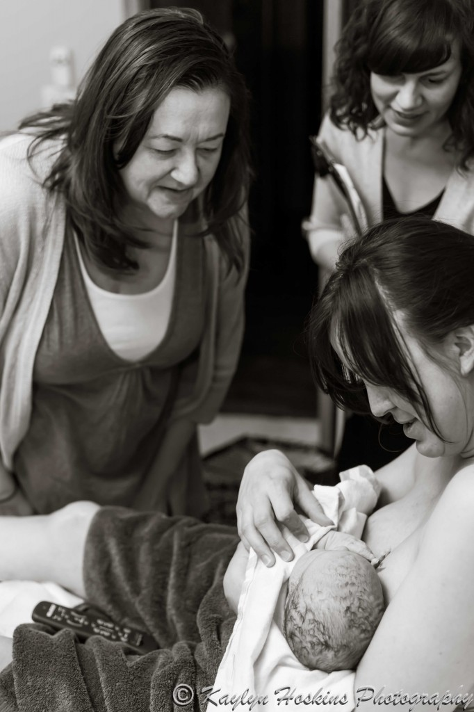 Midwives adore home water birthed baby boy with Mother holding him