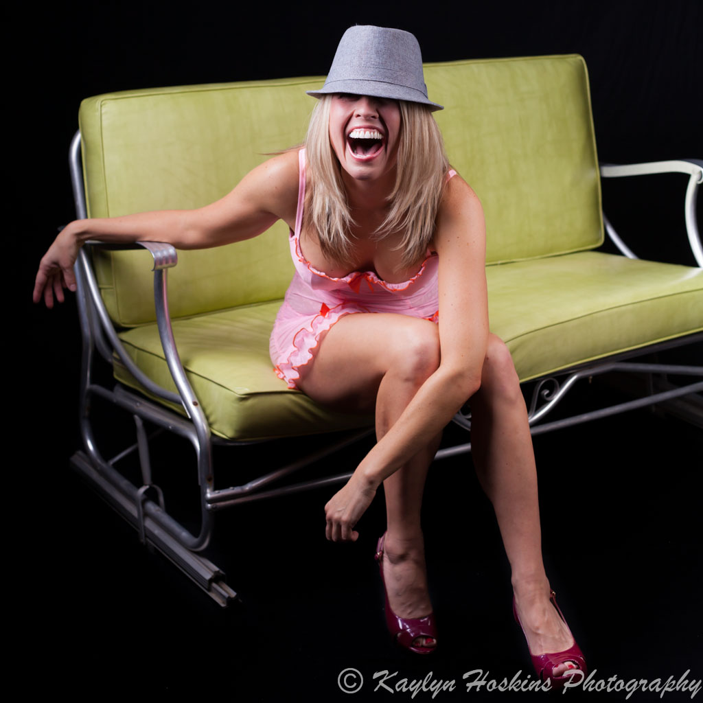 Beautiful woman laughs while sitting on end of green vintage love glider in pink lingerie