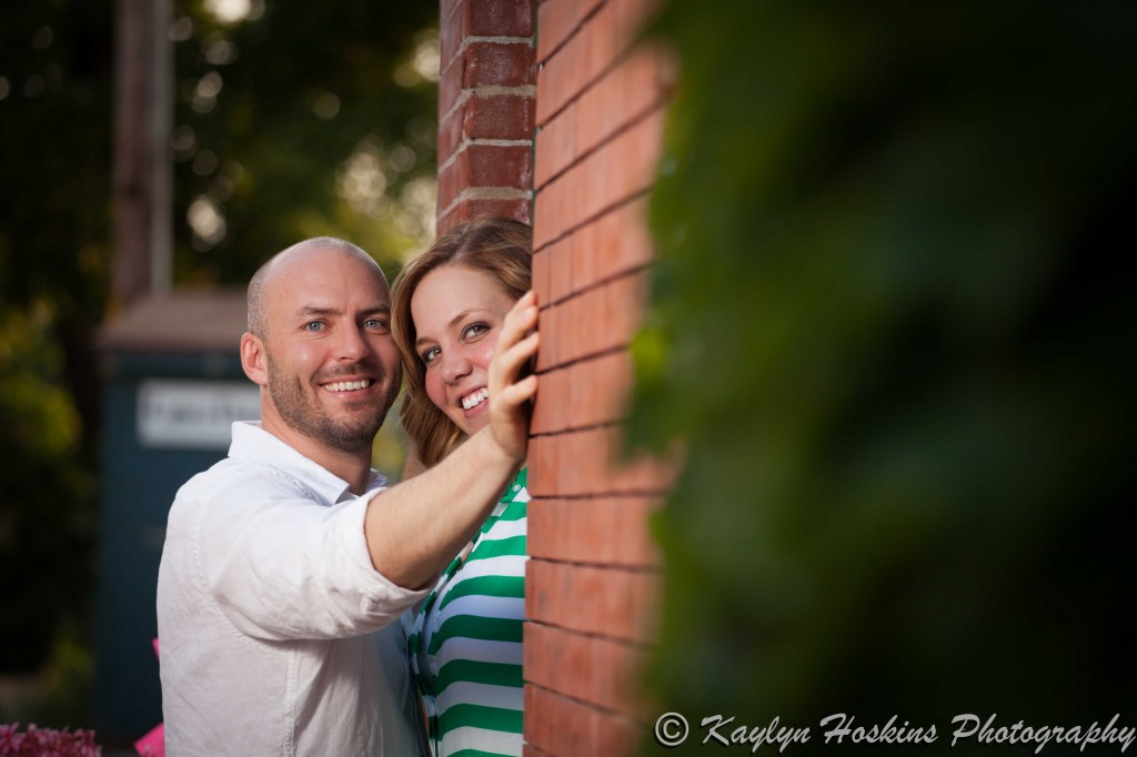 engagement couple peak out of doorway in New Bo Area during engagement photo shoot