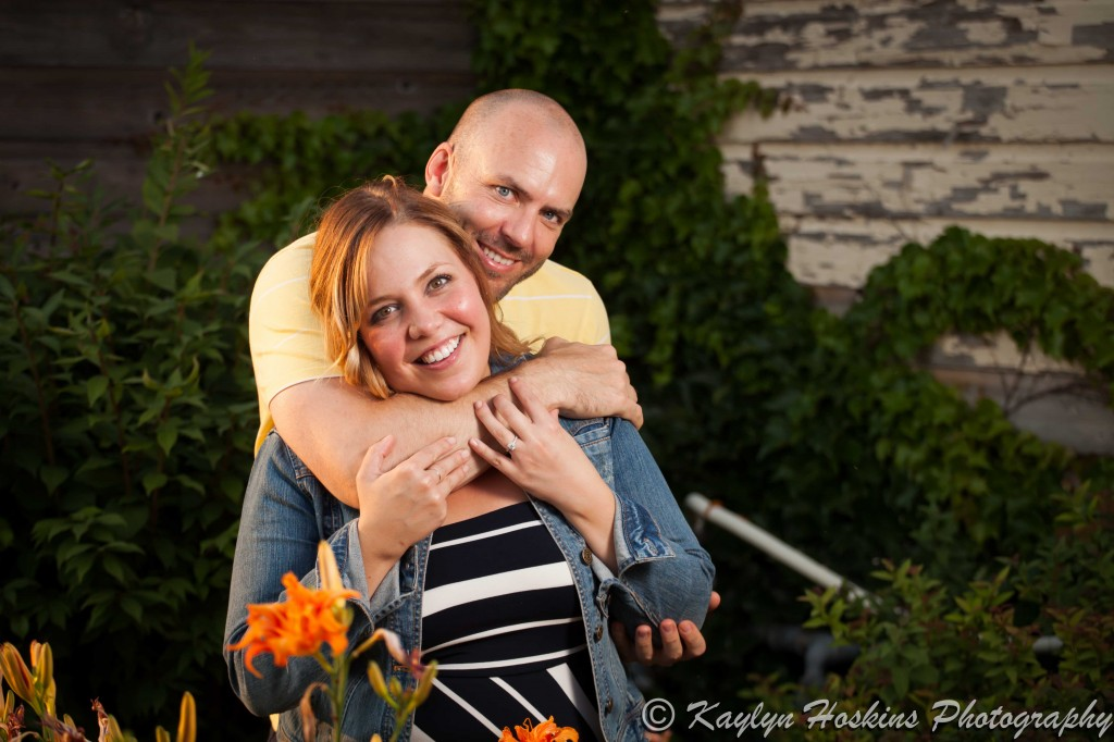 Man wraps his arms around his fiance during engagement photos in New Bo District