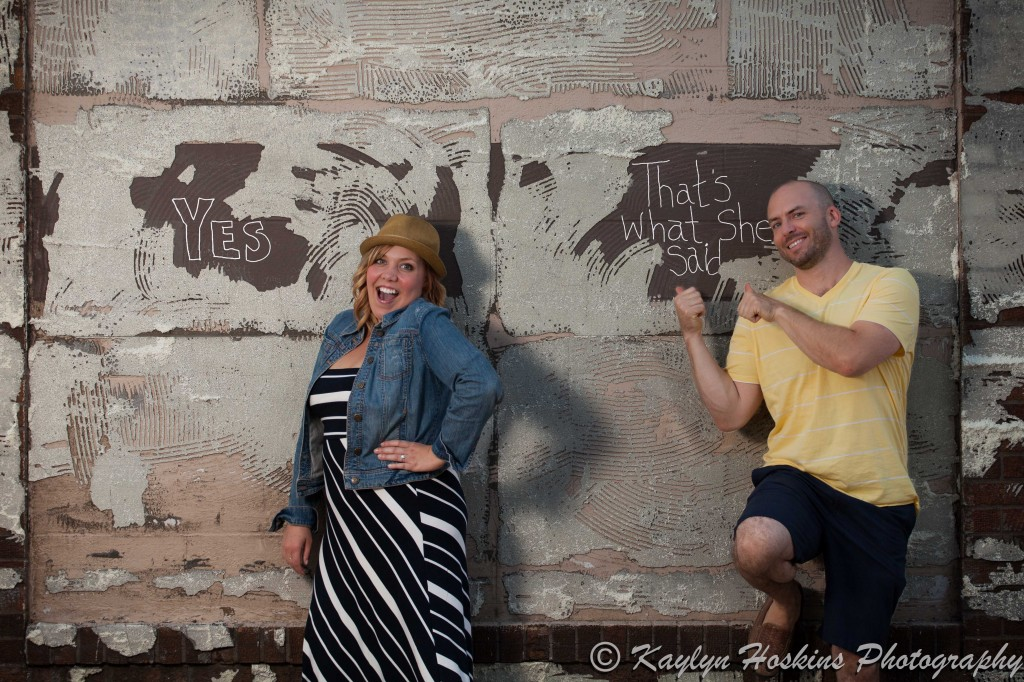 Engagement couple lean against wall after they wrote YES 'THAT'S WHAT SHE SAID' in Czech Village