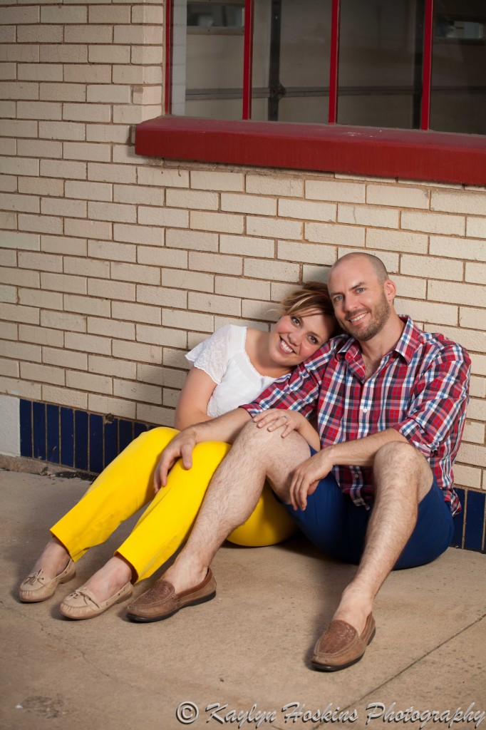 colorful engagement couple sitting against matching wall in Cedar Rapids Iowa