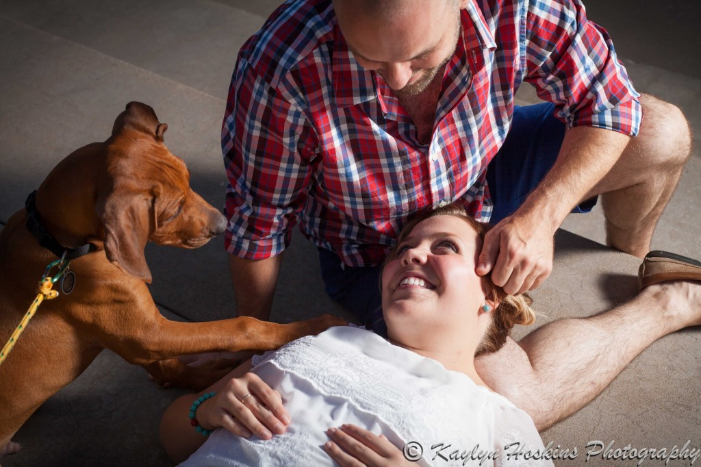 beautiful bride to be gets attention from her fiance while their puppy puts his paw on her during enagement photo session