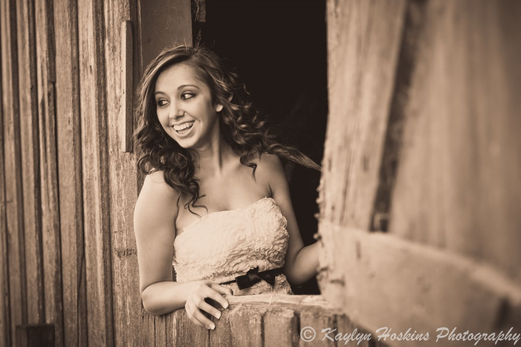 Beautiful Senior laughing while looking out old barn window during senior pics