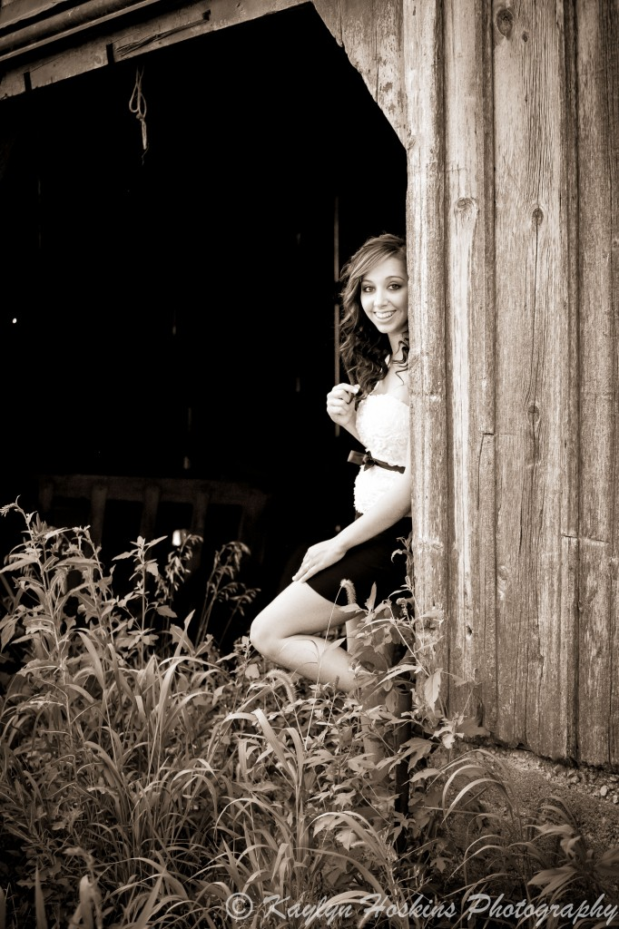 Addie peeks out of an old barn during her senior pics