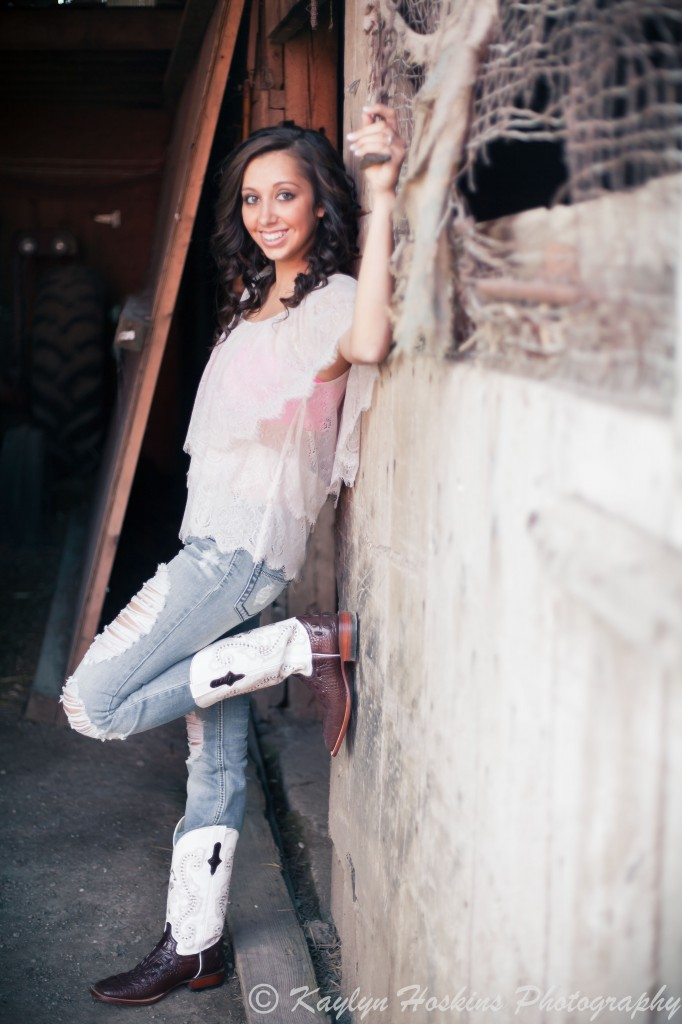 Beautiful Senior leans up against wall in old barn she grew up playing in during her Senior Pictures with Kaylyn Hoskins Photography