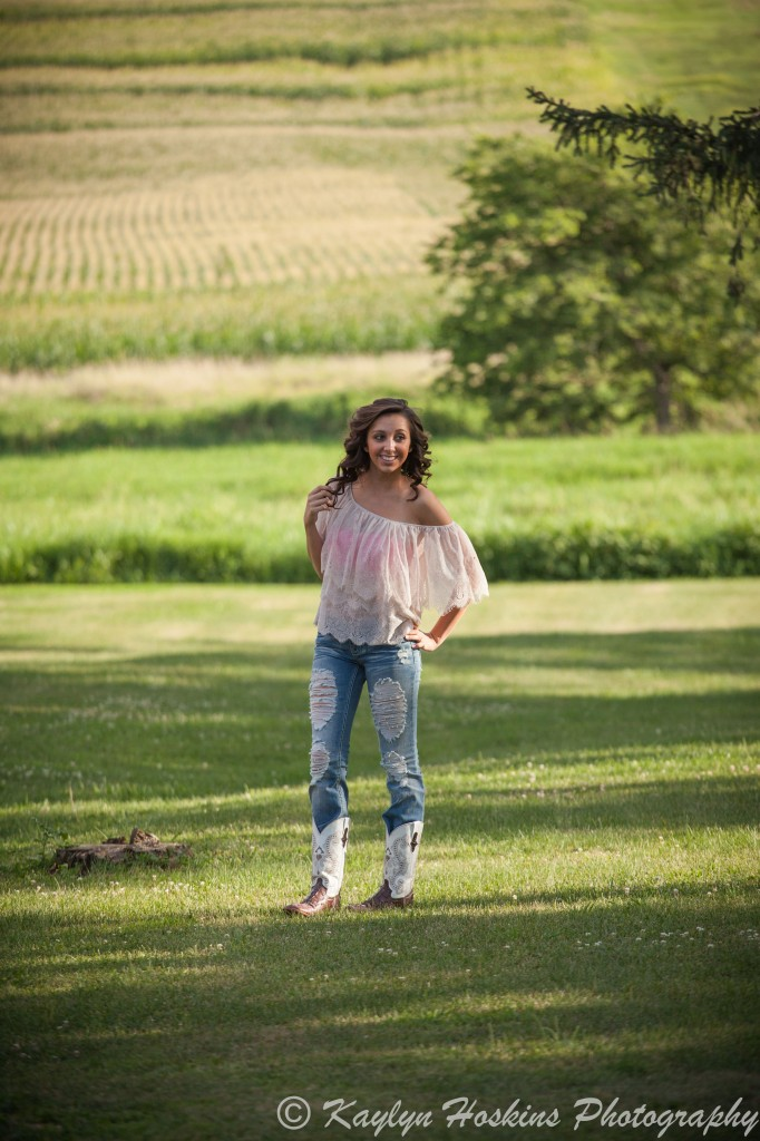 Solon Senior stands in field during her senior session with Kaylyn Hoskins Photography