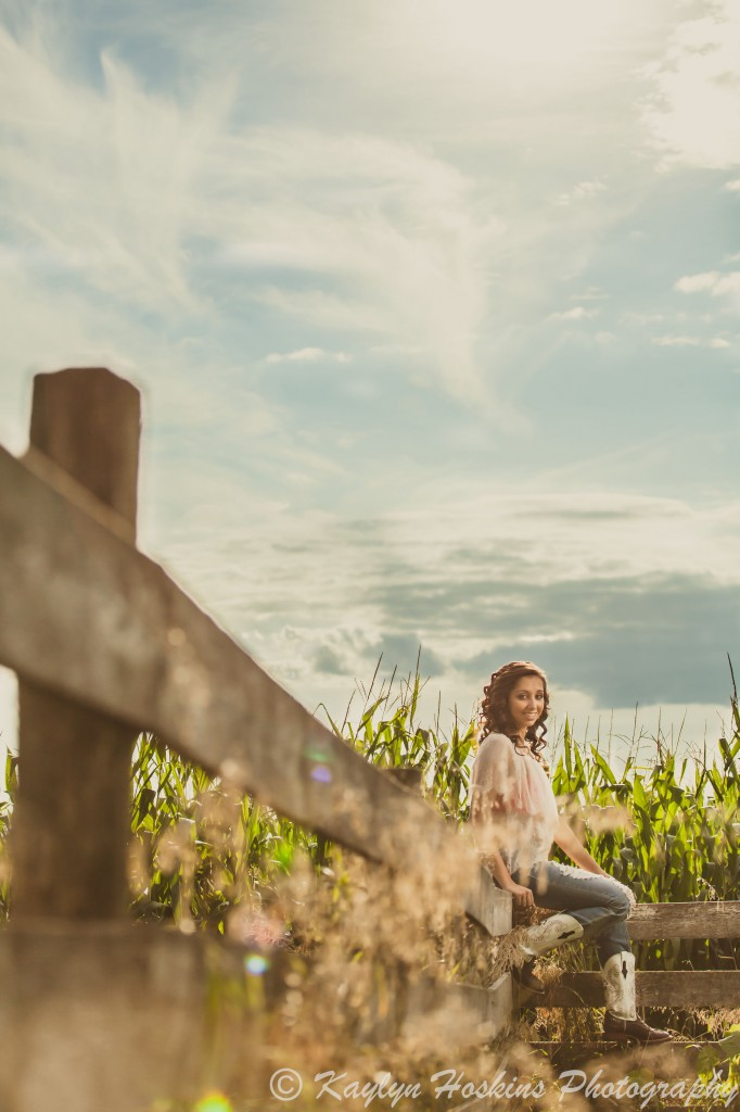 Solon senior sits on fence in front of corn field during her senior pics with Kaylyn Hoskins Photography