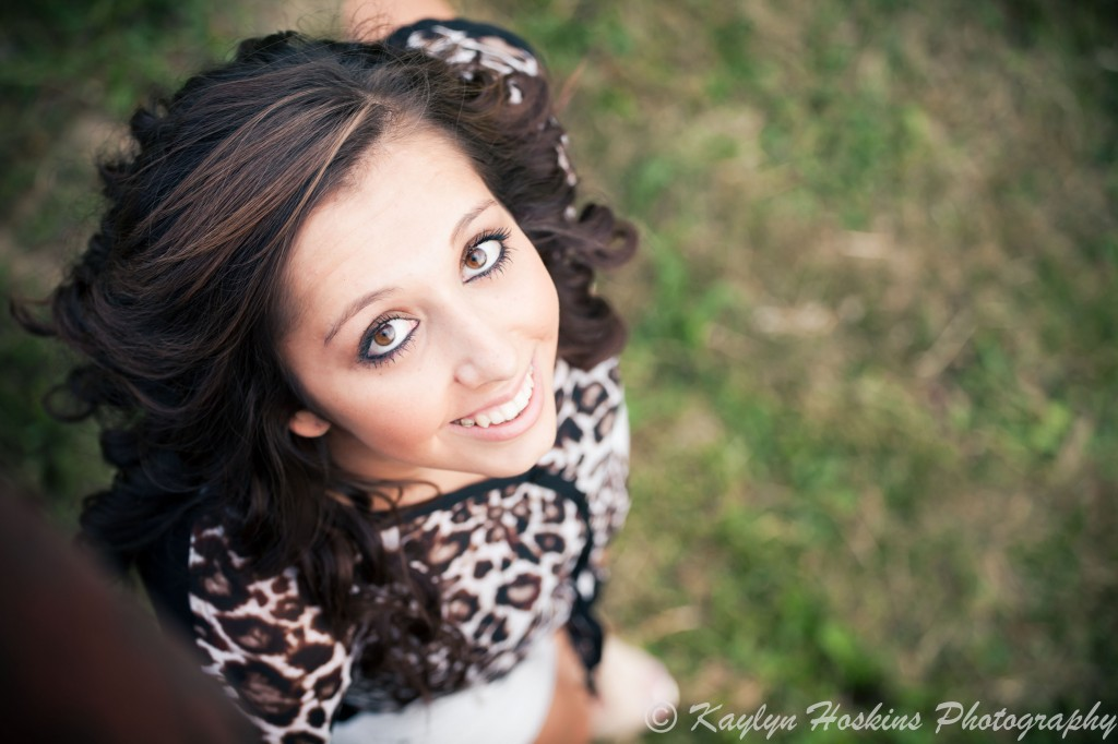 Gorgeous Senior smiles and looks up at the camera during senior photo session with Kaylyn Hoskins Photography at Harvest Preserve in Iowa City