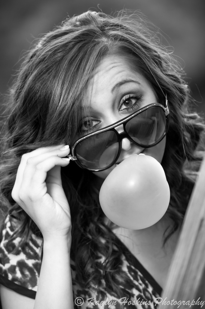 Solon Senior Addie blows a big league chew bubble gum bubble while looking over her glasses during senior pics session.
