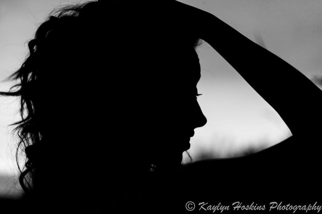 Solon Senior Addie runs hand thru her hair for a fun silhouette pic during her senior session with Kaylyn Hoskins Photography at Harvest Preserve in Iowa City