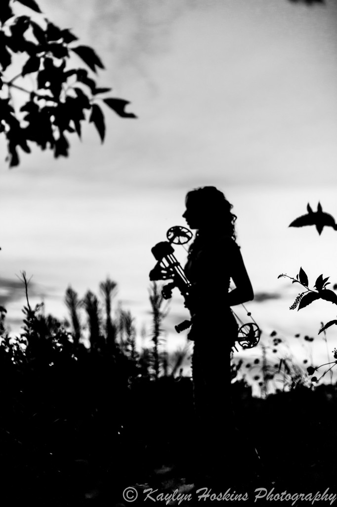 Beautiful HS Senior silhouetted with bow during Senior Pics at Harvest Preserve in Iowa City, IA