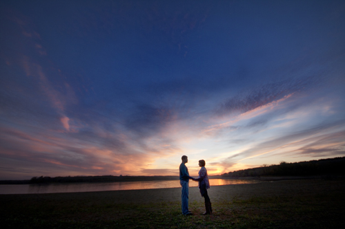 Engagement couple hold hands during sunset out at Lake MacBride Recreation Area in Iowa