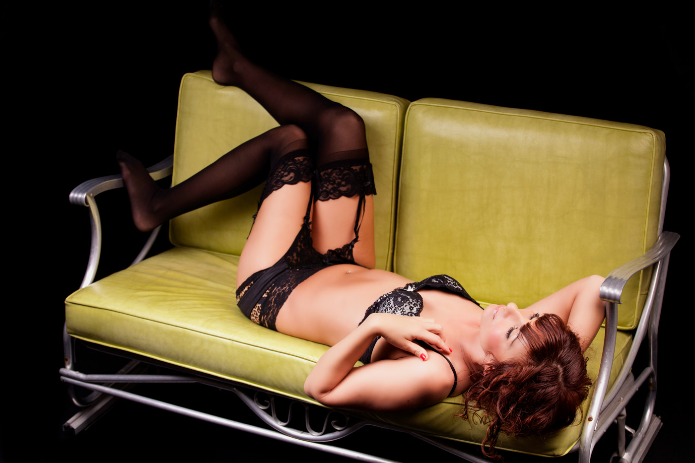 beautiful woman in lingerie laying on vintage love glider during boudoir experience