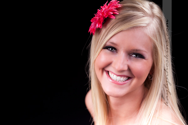 Lacie Joy genuinely smiles at the camera directed during her boudoir photography session with Kaylyn Hoskins Photography
