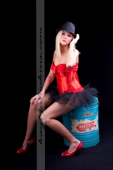 Lacie Joy adjusts her hat while sitting on an old bakerite container during boudoir shoot with Kaylyn Hoskins Photography