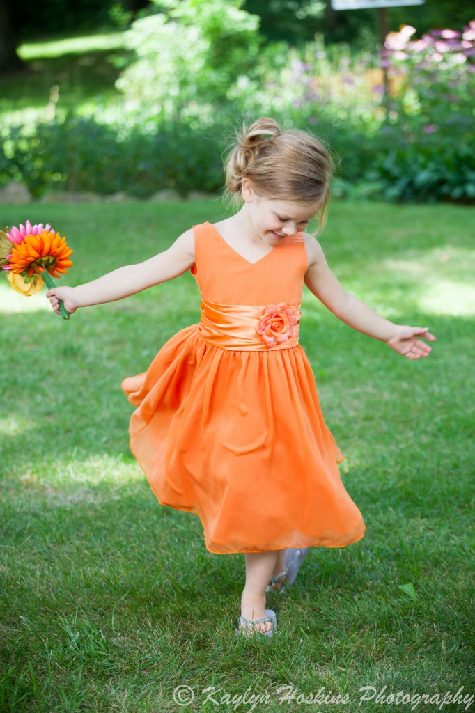 Beautiful little bridesmaid twirls in her dress before her Mom gets married at the Little Brown Church in Nashua, IA