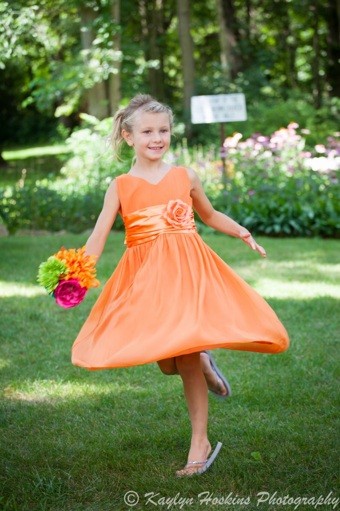 Beautiful bridesmaid twirls in her dress outside The Little Brown Church in Nashua, IA