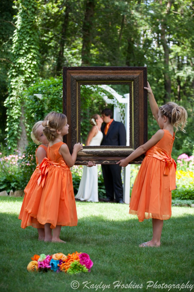 Beautiful bridesmaids hold a beautiful frame in front of the bride and groom outside the Little Brown Church