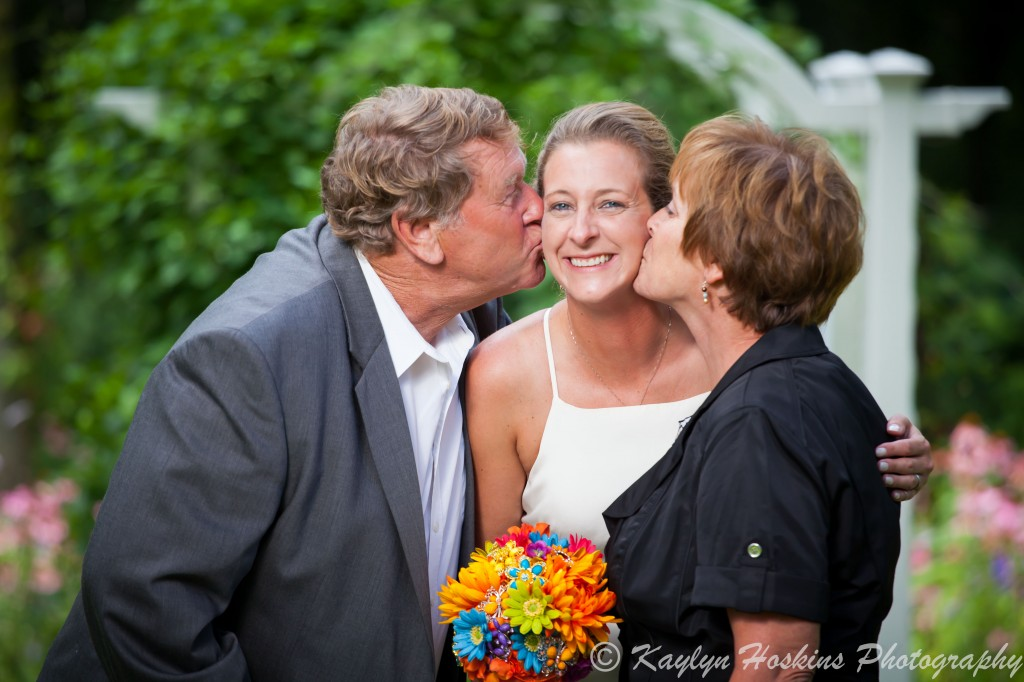 Beautiful Bride gets kisses from her Mom and Dad before walking down the isle at Little Brown Church in Nashua, IA