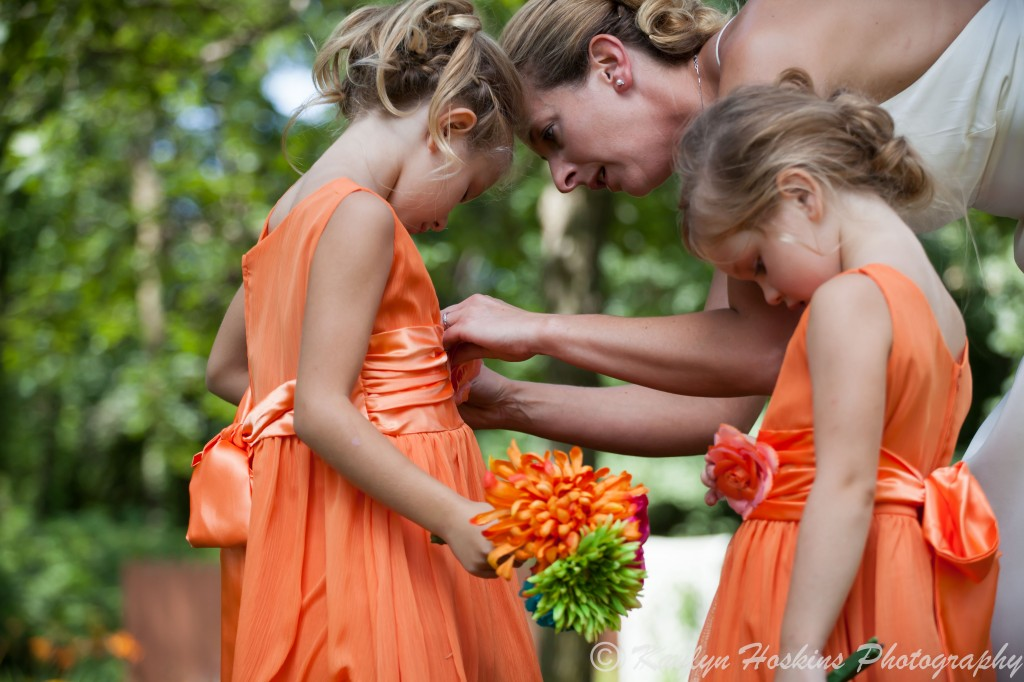 Bride helps little bridesmaid fix her dress before the ceremony