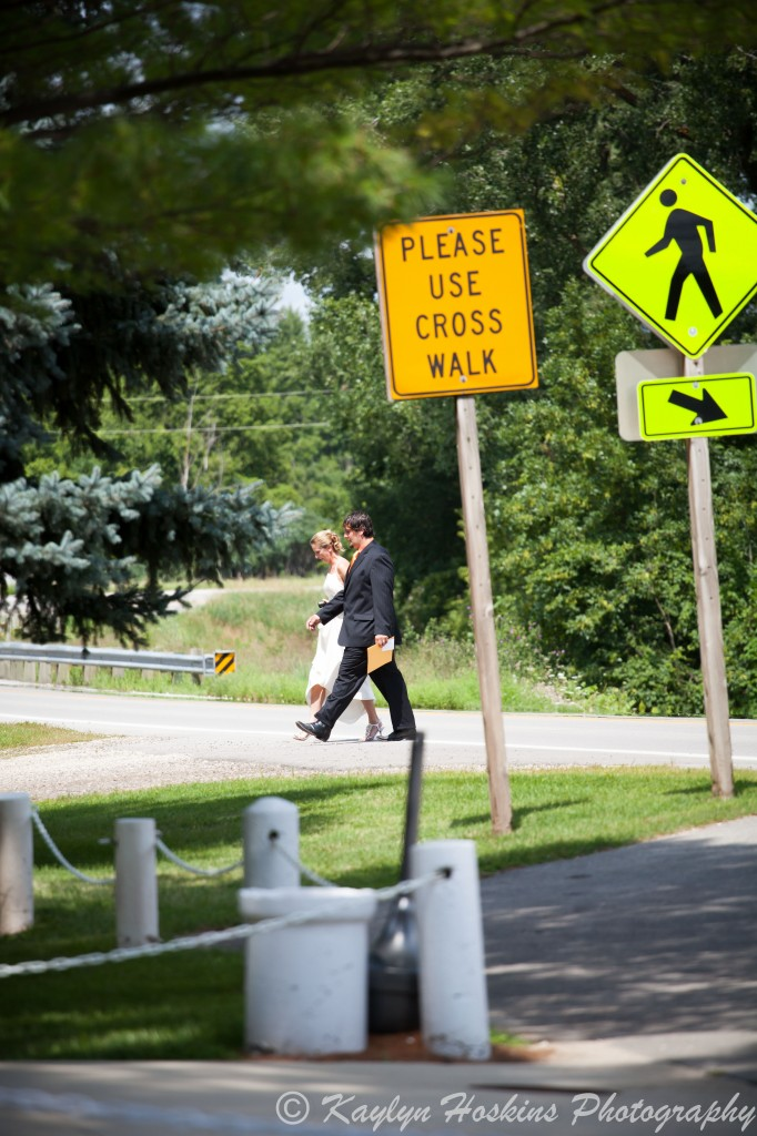Bride and groom walk across the road to get to the Little Brown Church before their wedding.