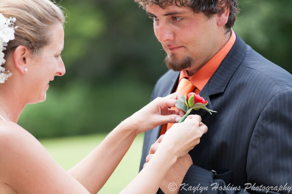 Bride pins on groom's corsage before wedding ceremony at The Little Brown Church in Nashua