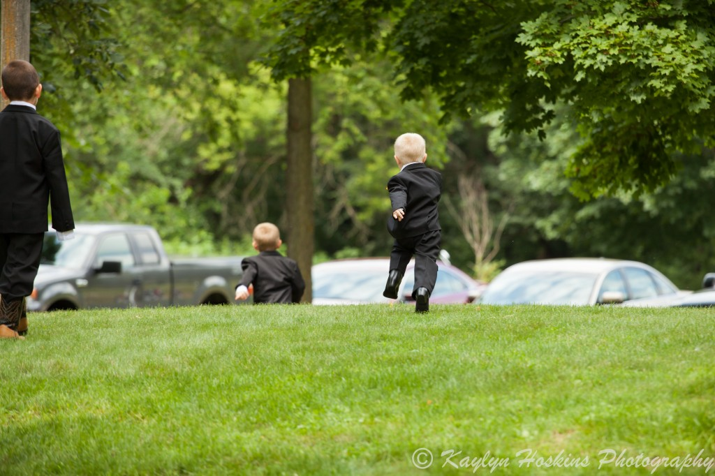 Little ring bearer runs around outside church before wedding at The Little Brown Church in Nashua, IA