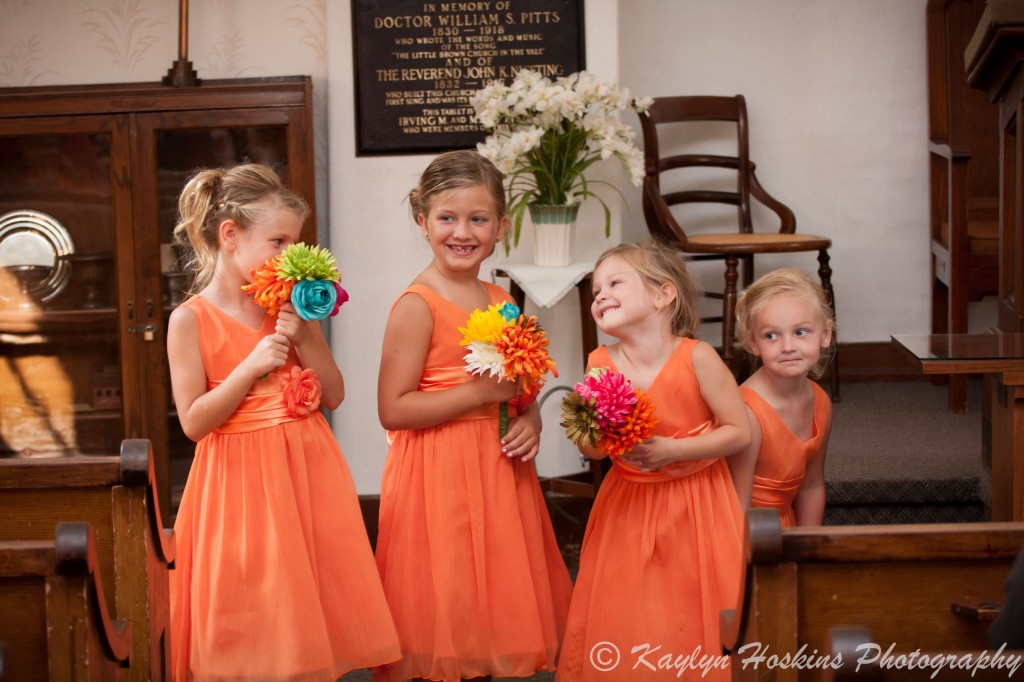 The young bridesmaids having fun during wedding ceremony at the Little Brown Church in Nashua, IA