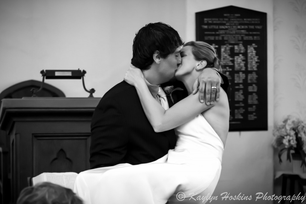 Groom picks up bride for a spectacular kiss at the Little Brown Church in Nashua