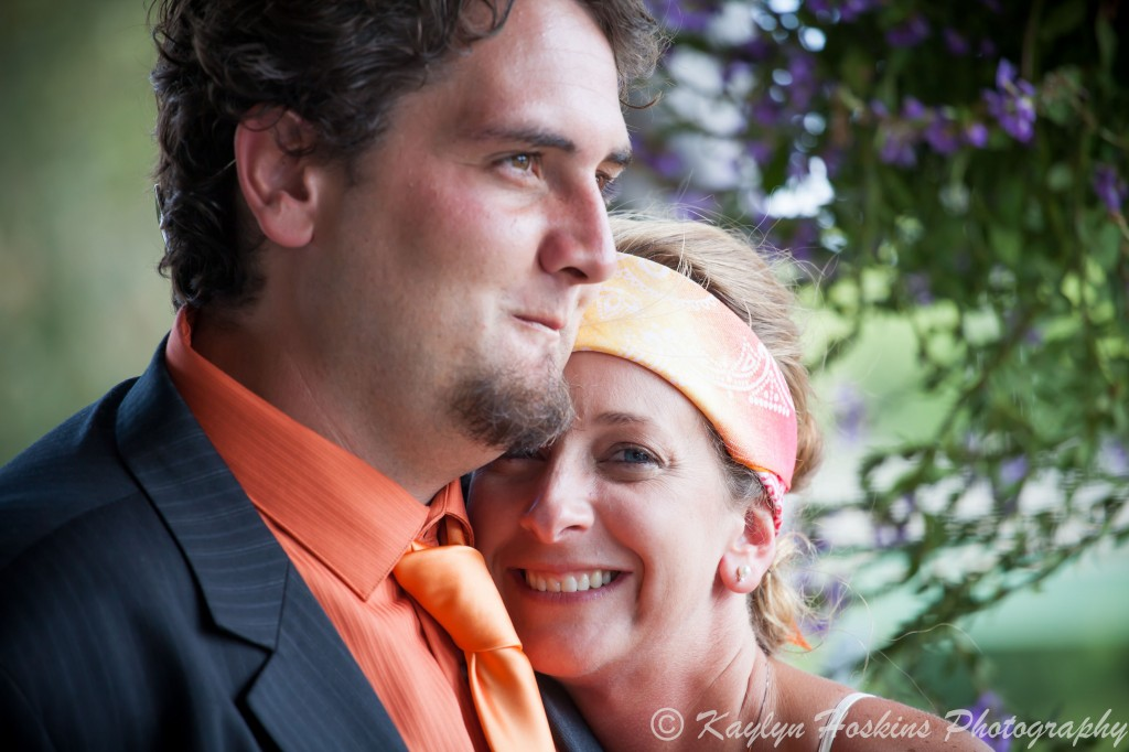 Gorgeous bride smiles as she leans on grooms shoulder