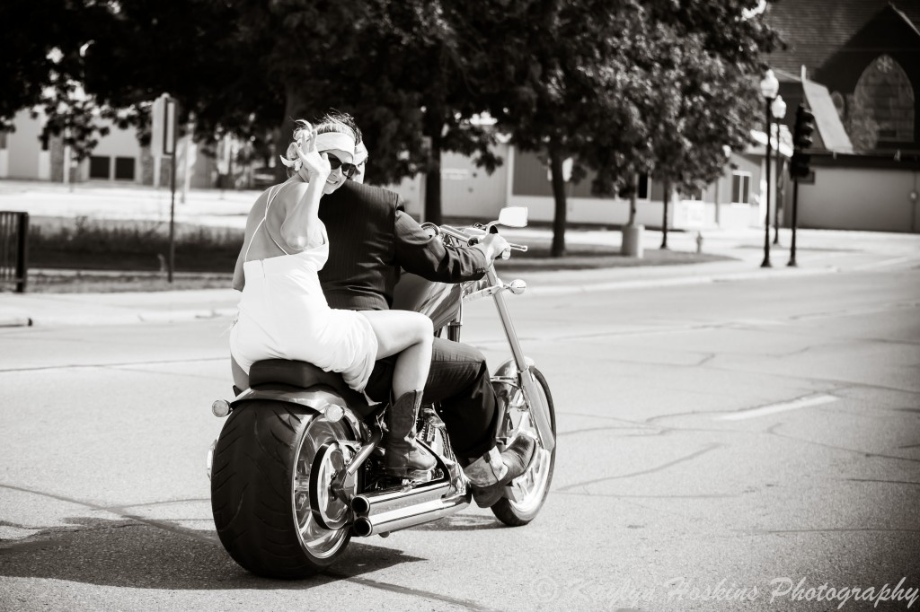 Bride waves as the groom zooms away on a Harley to get to their wedding reception in Iowa