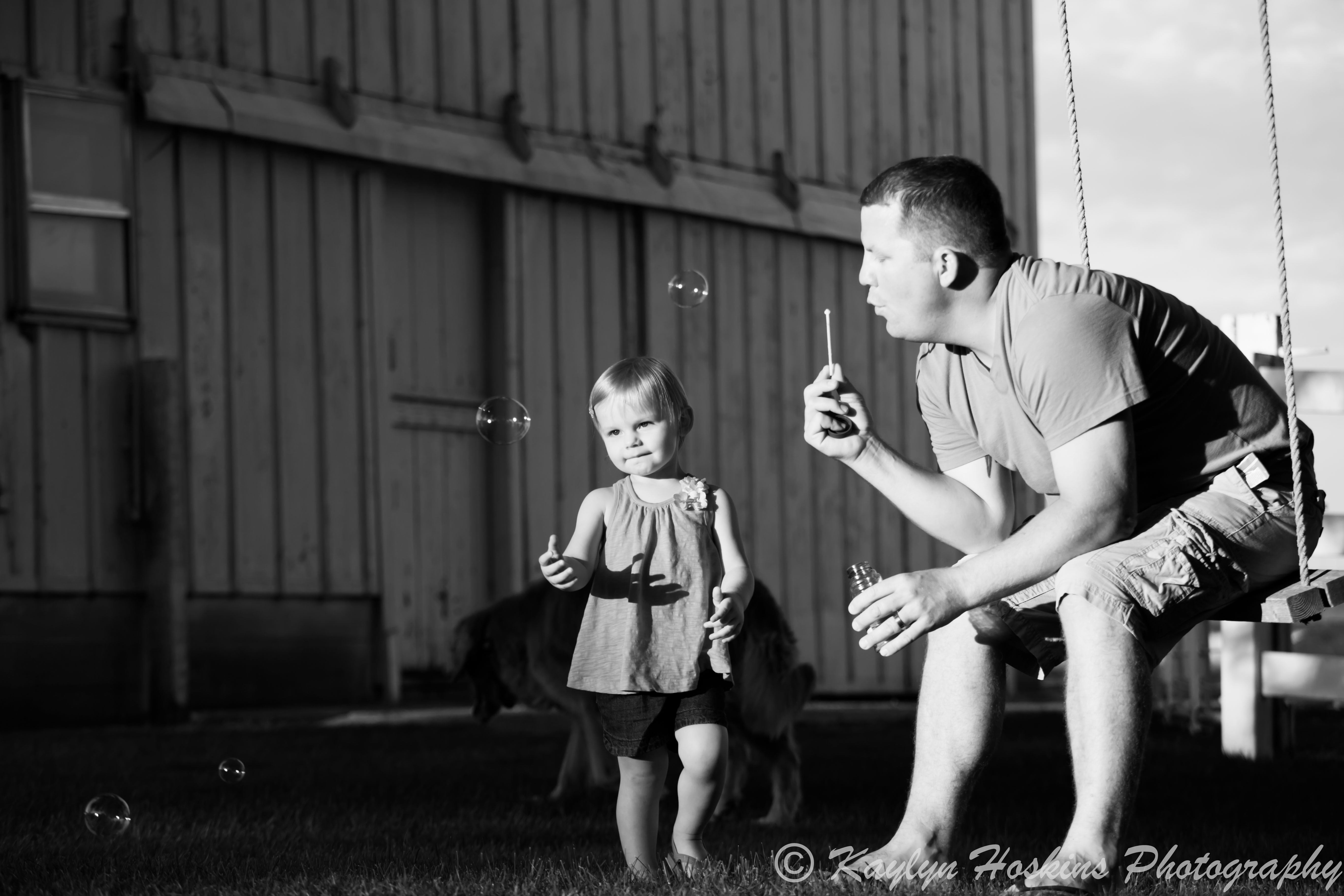 Dad blows bubbles for daughter to catch during family photos
